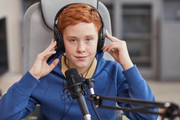 Vue de face portrait d'un adolescent aux cheveux rouges parlant au microphone et portant des écouteurs lors de l'enregistrement d'un podcast ou d'une diffusion en ligne