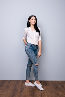 Vue de face, portrait complet de jeune fille jolie joyeuse tenant la main dans la poche de son jean et posant contre l'espace gris