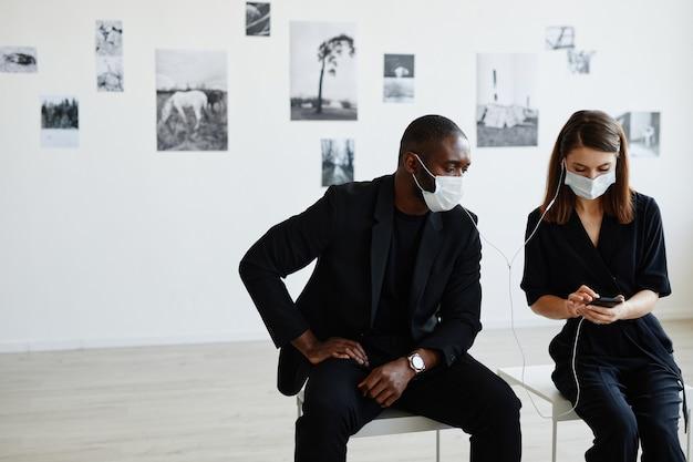 Vue de face portrait d'un couple élégant portant des masques lors de l'utilisation d'un smartphone avec visite audio dans une galerie d'art moderne, espace pour copie