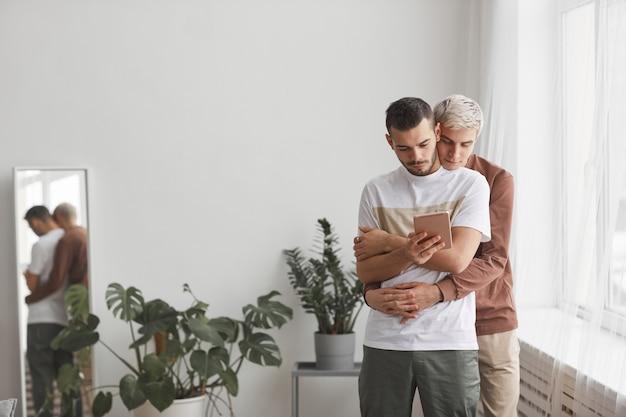 Vue de face portrait d'un couple gay contemporain embrassant tout en regardant l'écran de la tablette dans un intérieur minimal de la maison, espace de copie