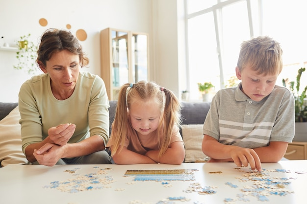 Vue de face portrait de famille aimante avec enfant ayant des besoins spéciaux jouant avec des puzzles et des jeux de société ensemble à la maison, copiez l'espace