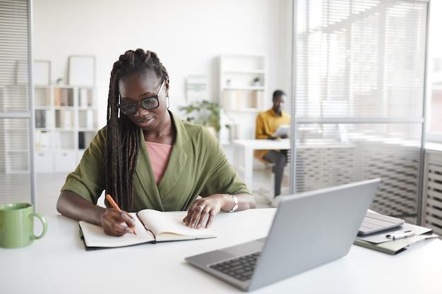 Vue de face portrait de femme afro-américaine contemporaine écrit dans le planificateur tout en travaillant au bureau dans l'intérieur de bureau blanc, espace copie