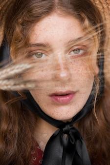 Vue de face portrait de femme avec chapeau de paille