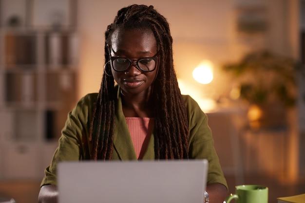 Vue de face portrait de jeune femme afro-américaine à l'aide d'un ordinateur portable tout en travaillant au bureau ou à la maison éclairée par un éclairage tamisé confortable, copiez l'espace