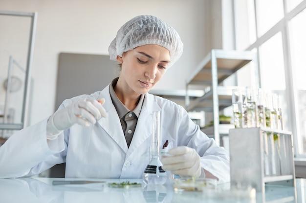Vue de face portrait de jeune femme scientifique effectuant des expériences avec des échantillons de plantes tout en travaillant sur la recherche en laboratoire de biotechnologie, copy space