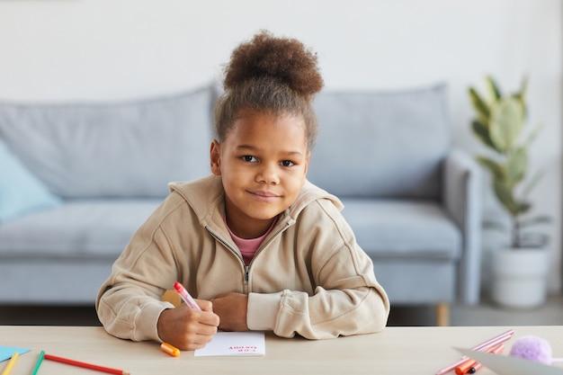 Vue de face portrait d'une jolie fille afro-américaine dessinant des images et souriant à la caméra alors qu'elle était assise au bureau dans un intérieur confortable, espace pour copie