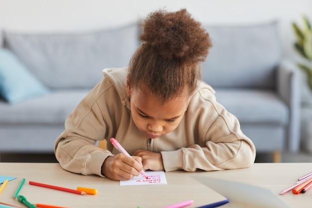 Vue de face portrait d'une jolie fille afro-américaine signant une carte faite à la main comme cadeau pour la fête des pères, espace pour copie