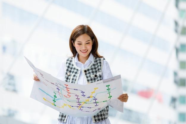 Vue de face portrait d'une jolie jeune femme asiatique adulte souriante dans des vêtements de mode décontractés debout, tenant et regardant une carte de métro en papier pour planifier un chemin vers la destination avec un arrière-plan flou