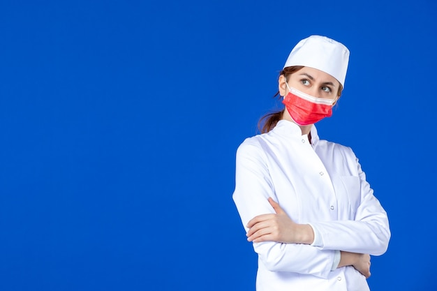 Vue de face posant jeune infirmière en costume médical avec masque rouge sur bleu