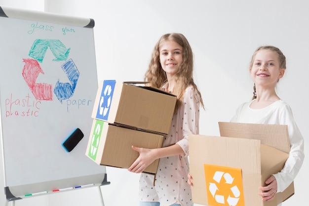 Vue de face positive jeunes filles tenant des boîtes de recyclage