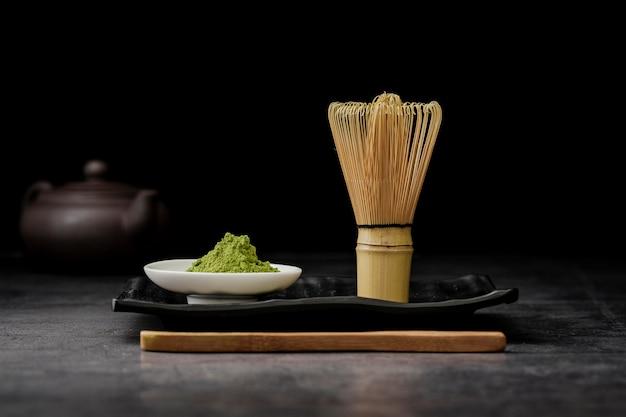 Vue de face de la poudre de thé matcha avec un fouet en bambou