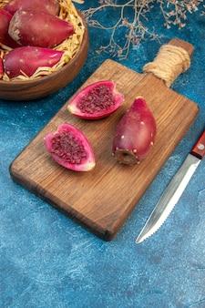 Vue de face prunes fraîches mûres à l'intérieur de la plaque sur fond bleu photo aigre couleur fruit moelleux santé exotique