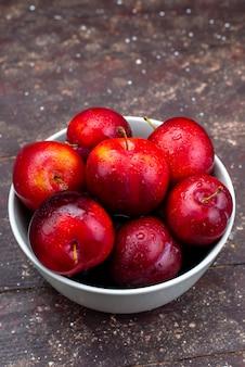 Une vue de face de prunes rouges fraîches moelleuses et mûres à l'intérieur de la plaque blanche sur le jus de fruits de bureau en bois