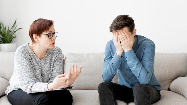 Vue de face d'un psychologue consultant un patient
