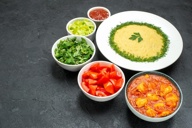 Vue de face de la purée de pommes de terre avec des légumes verts et des tomates tranchées sur un espace gris
