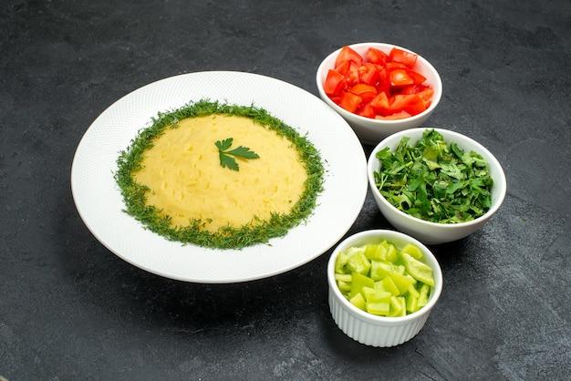 Vue de face de la purée de pommes de terre avec des légumes verts et des tranches de tomates fraîches sur un espace gris