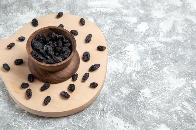 Vue de face raisin noir séché sur espace blanc