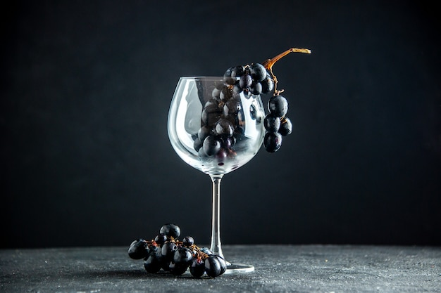 Vue de face des raisins frais dans un verre à vin sur un espace libre de table sombre