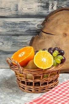 Vue de face des raisins de fruits frais et des tranches d'oranges à l'intérieur du panier sur fond blanc fruits mûrs mûrs vitamine frais