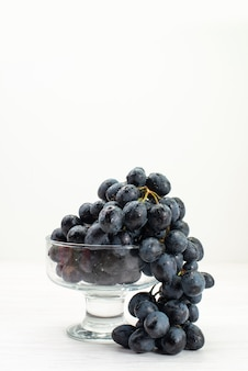 Vue de face des raisins noirs frais sur la surface blanche fruits frais jus moelleux