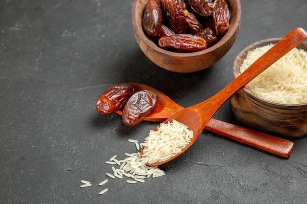 Vue de face des raisins secs avec du riz cru sur la surface sombre des fruits secs aux raisins secs