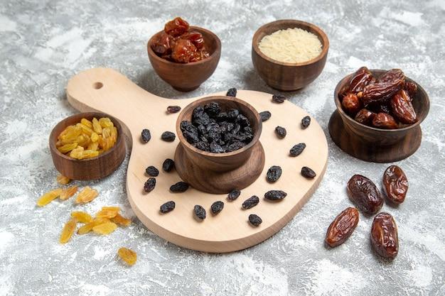 Vue de face de raisins secs noirs avec différents raisins secs sur un espace blanc