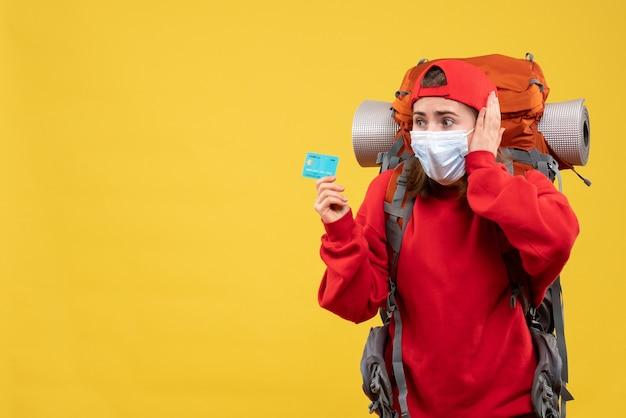 Vue de face de la randonneuse perplexe avec sac à dos et masque tenant la carte de crédit