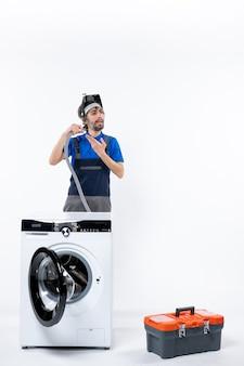 Vue de face d'un réparateur confus en uniforme debout derrière une machine à laver tenant un tuyau en plastique sur un mur blanc