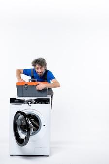 Vue de face réparateur masculin mettant le sac d'outils sur la machine à laver sur l'espace blanc