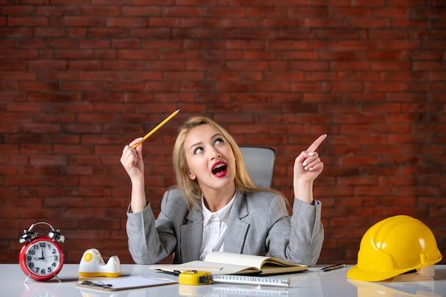 Vue de face rêvant ingénieur féminin assis derrière son lieu de travail