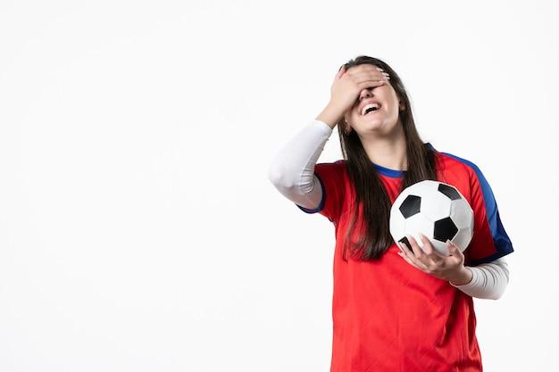 Vue de face en riant jeune femme en vêtements de sport avec ballon de foot