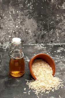 Vue de face riz cru avec de l'huile sur la surface sombre du riz photo noir