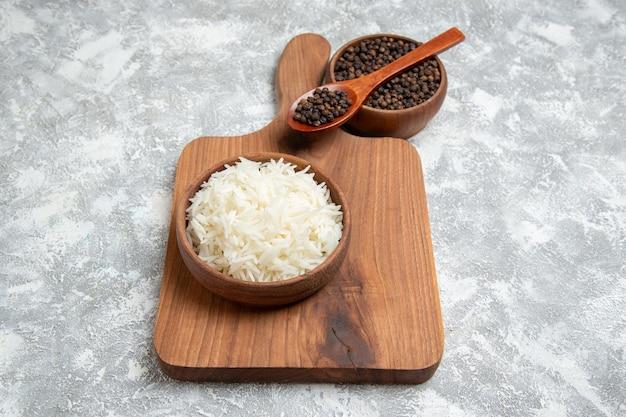 Vue de face riz cuit délicieux avec du poivre sur un espace blanc