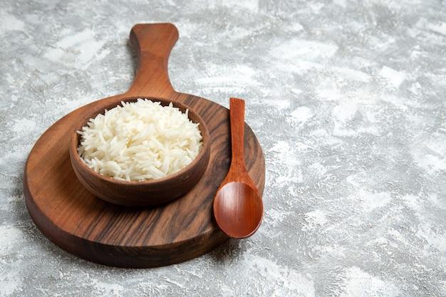 Vue de face riz cuit délicieux à l'intérieur d'une assiette brune sur un espace blanc