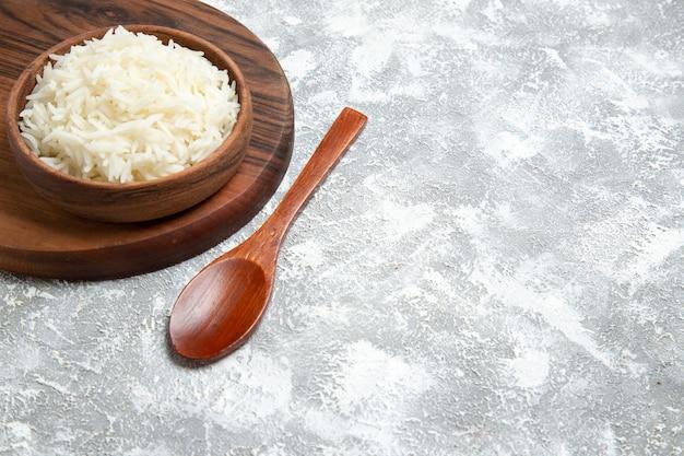 Vue de face riz cuit délicieux à l'intérieur de la plaque sur un espace blanc