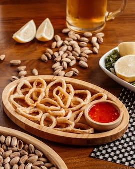 Une vue de face des rondelles d'oignon avec de la bière sauce aux arachides sur la table en bois brun snack-repas