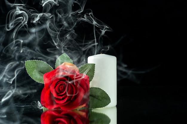 Vue de face d'une rose rouge avec une bougie blanche sur fond noir