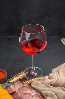 Vue de face d'une rose rouge dans un gobelet en verre, des collations à la rose rouge et du poivre sur fond sombre