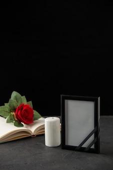 Vue de face de la rose rouge avec livre et cadre photo sur fond noir