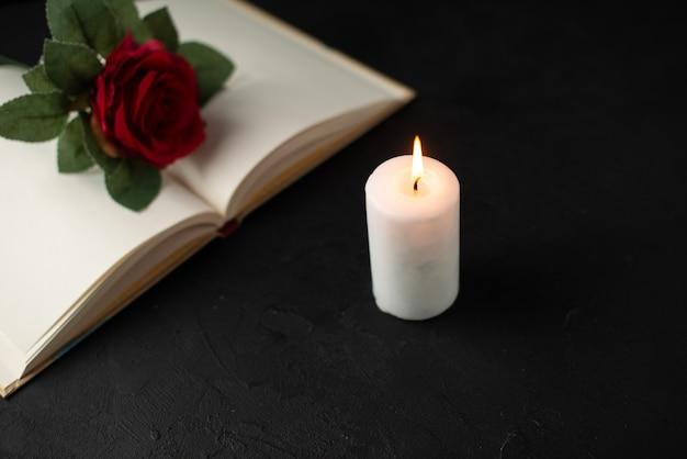 Vue de face de rose rouge avec livre ouvert et bougie sur fond noir