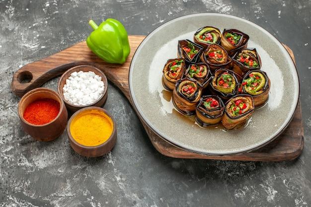 Vue de face rouleaux d'aubergines farcies dans une assiette ovale grise un poivron vert sur une planche de service en bois avec poignée différentes épices dans de petits braillements sur fond gris