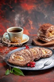 Vue de face des rouleaux de biscuits avec une tasse de thé sur une surface sombre