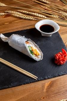 Une vue de face des rouleaux de poisson remplis de légumes en tranches de riz avec de la farine de poisson sauce au japon