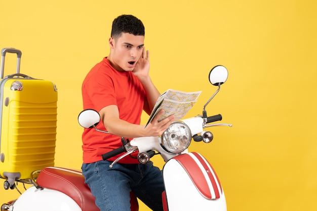 Vue de face s'est demandé jeune homme sur un cyclomoteur en regardant la carte