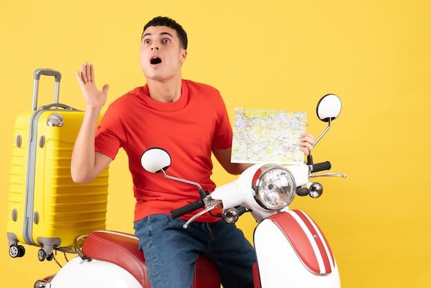 Vue de face s'est demandé jeune homme en vêtements décontractés sur un cyclomoteur tenant une carte de voyage