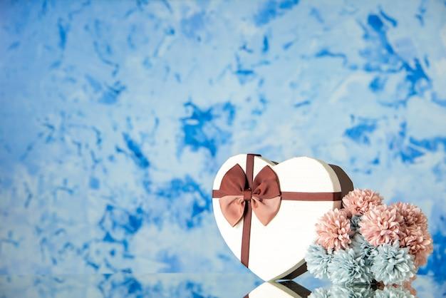 Vue de face saint valentin présent avec des fleurs sur fond bleu clair mariage couleur passion famille beauté amour sentiment