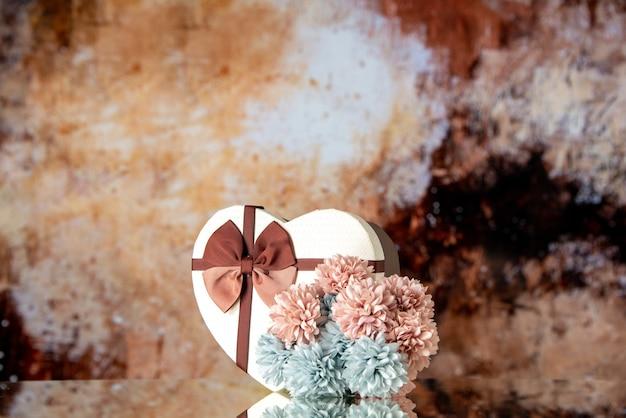 Vue de face saint valentin présent avec des fleurs sur fond marron clair sentiment de beauté famille couple passion amour coeur