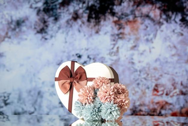 Vue de face saint valentin présente avec des fleurs sur fond clair sentiment de couleur beauté famille passion amour coeur