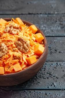 Vue de face salade de carottes fraîches salade râpée aux noix et à l'ail sur le bureau sombre régime alimentaire salade de noix couleur santé