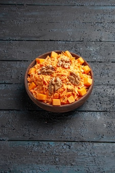 Vue de face salade de carottes fraîches salade râpée aux noix et à l'ail sur le bureau sombre régime salade mûre couleur santé
